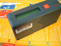 A gloss measurement device which is a small box with a screen on it.