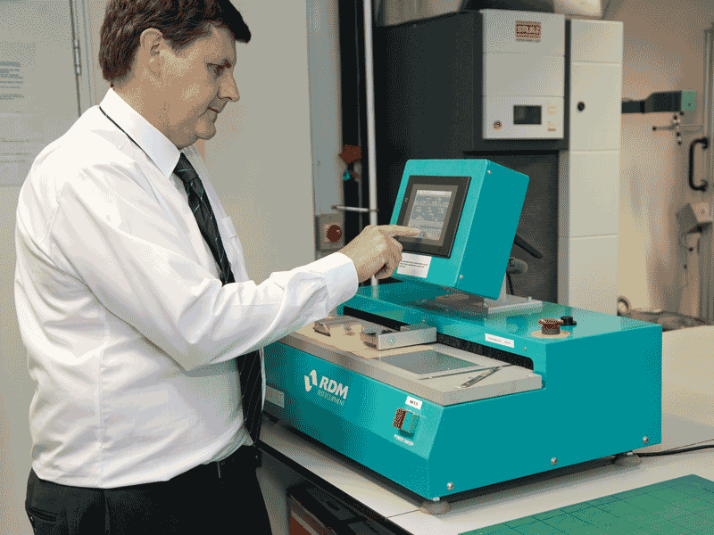 An expert at Smithers using a teal coloured paper slip coefficient machine.